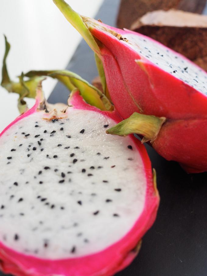 Halkasitu pitahaya-hedelmä ja taustalla raakasuklaamassan palasia