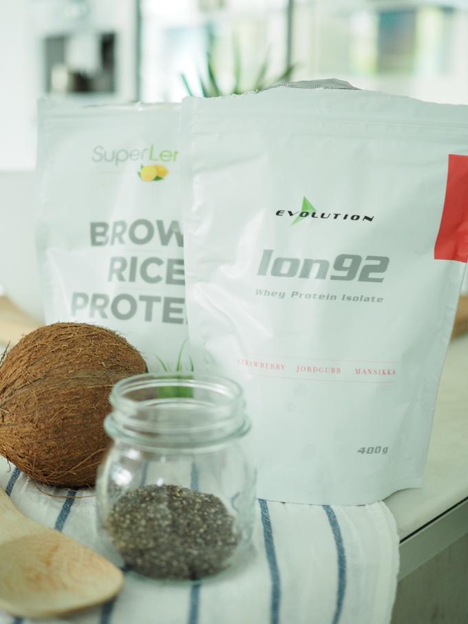 Proteiini-chia-kookosvanukkaan raaka-aineet eli luomulaatuinen riisiproteiini, laktoositon heraproteiini-isolaatti, kookospähkinä ja chia-siemeniä lasipurkissa