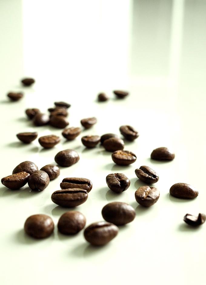 Kahvipapuja vaalealla taustalla