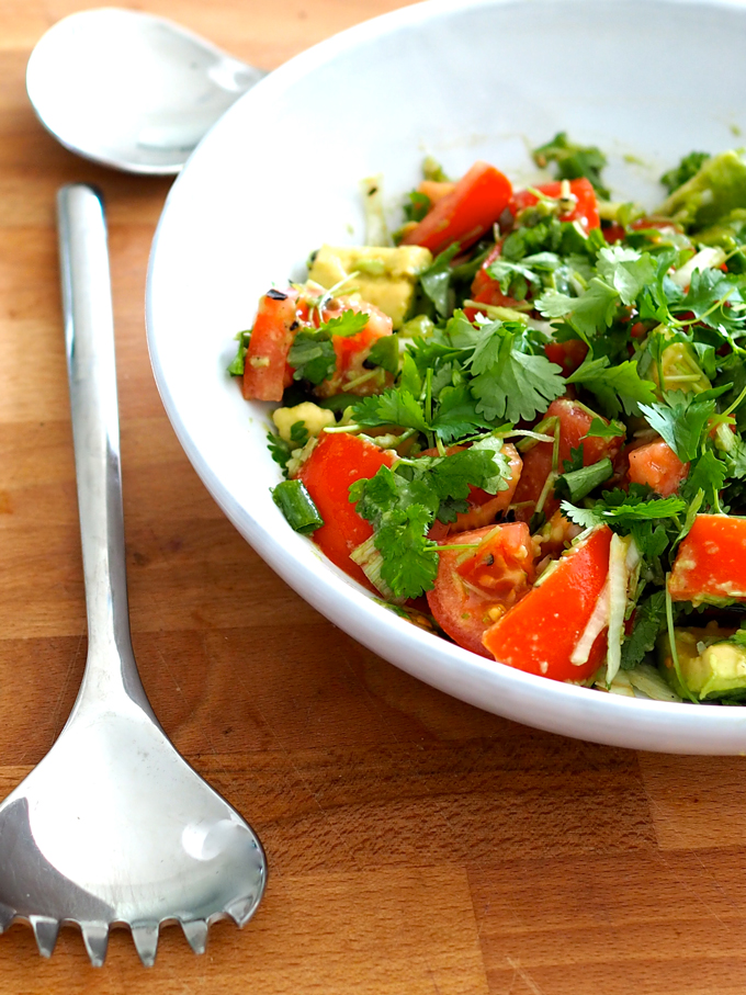 Tomaatti-avokadosalaatti valkoisella lautasella ottimet vieressä