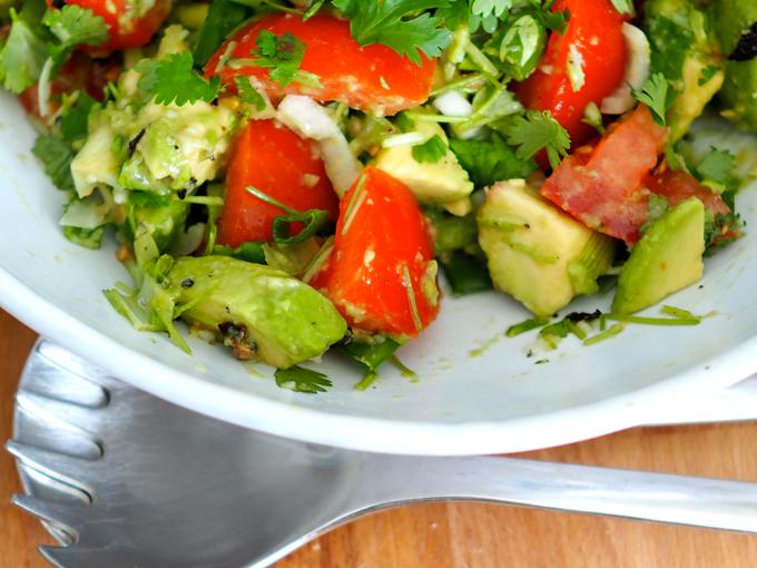 Tomaatti-avokadosalaatti valkoisella lautasella